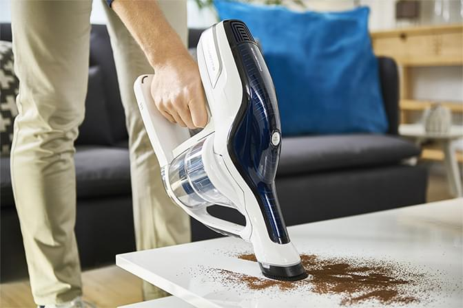 Man vacuuming on a table